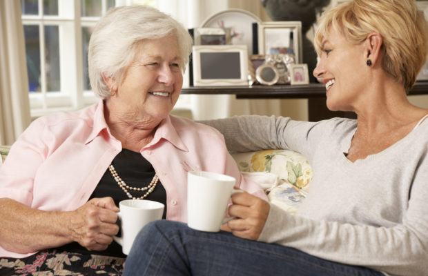 Adult Daughter Visiting Senior Mother Sitting On Sofa At Home